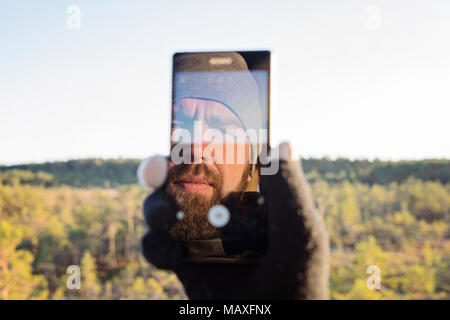 Bearded man taking selfie looking at smartphone display nature forest background, close up - Stock Photo