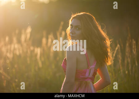 Portrait of a beautiful young woman in meadow at sunset - Stock Photo