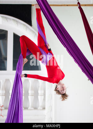 Young attractive air gymnast performs an exercise hanging on aerial silk - Stock Photo