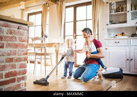 Father and two toddlers doing housework. - Stock Photo