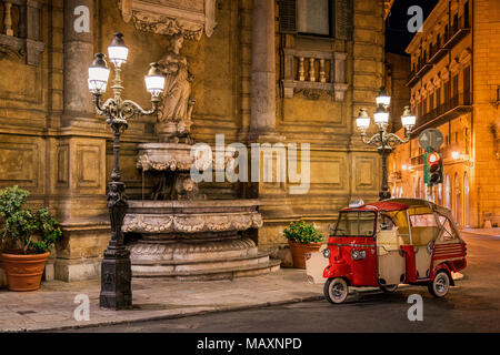 Quattro Canti in Palermo Sicily at night with a red 3 wheeled taxi parked on the corner, of the four fountains this is the north-east one with the sta - Stock Photo