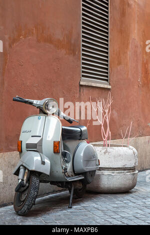 A classic grey coloured Vespa scooter parked in the back streets of Rome, Italy. - Stock Photo