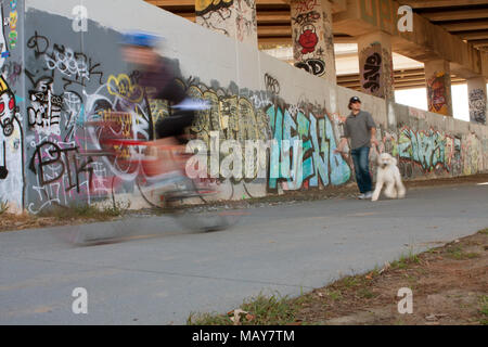 Motion blur of people exercising along a graffiti covered trail that is part of the Atlanta Beltline, on November 2, 2013 in Atlanta, GA.