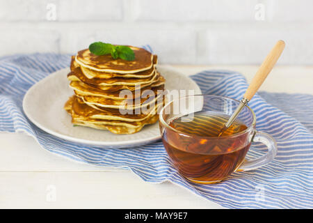 fresh baked pancakes with mint in white plate and cup of tea on blue linen on white background - Stock Photo