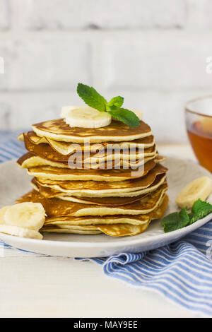 fresh baked pancakes with banana in white plate and cup of tea on blue linen on white background - Stock Photo