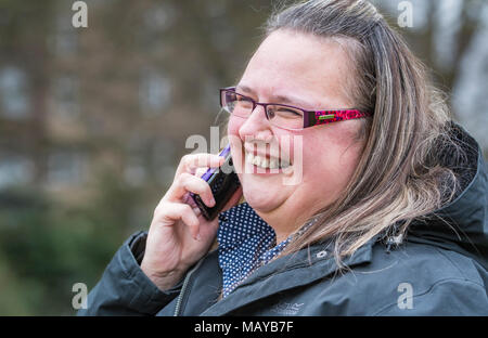 Young woman smiling and looking happy while speaking on a mobile phone. Happiness concept. Pleasing news. Happy news. - Stock Photo