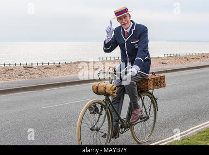 Elderly man cycling on a Victorian bicycle dressed in period costume wearing a blazer and straw boater hat, in the UK. Gentleman tipping hat. - Stock Photo