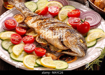 Roasted dorada fish with vegetables on wooden background - Stock Photo