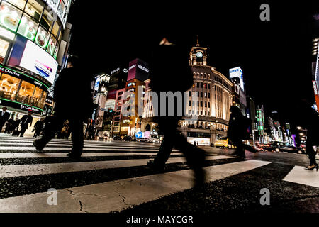 Tokyo, Japan. Pedestrians crossing the street at the heart of Ginza District in Tokyo. Ginza crossing at night. Blurred motion. - Stock Photo
