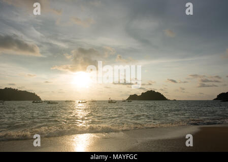 view of a sunset sky and silhouette of floating boats and small island on the beach as foreground located in Pangkor island, perak, malaysia - Stock Photo