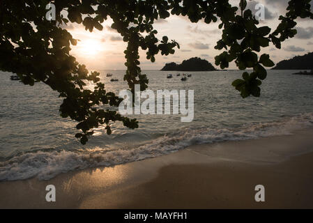 sunset view of a beach with silhouette of tree, boats and small island located in Pangkor island, perak, malaysia - Stock Photo