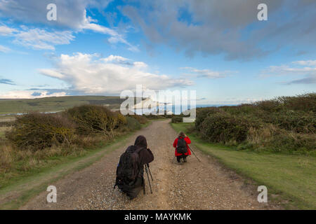 Two photographers with tripods at Seaford photographing the classic view of the Seven Sisters chalk cliffs on the South Downs Way, East Sussex, UK. - Stock Photo