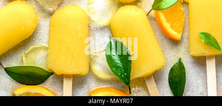 Orange popsicle with juice iced on stick, natural refreshing ice cream dessert for summer - Stock Photo