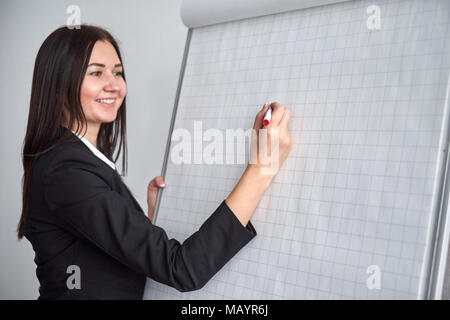close up of woman with marker writing or drawing something on flip chart. - Stock Photo