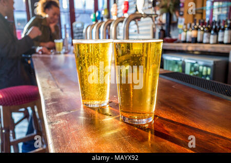 Close up of two pints of lager on the bar of a pub, UK, London - Stock Photo