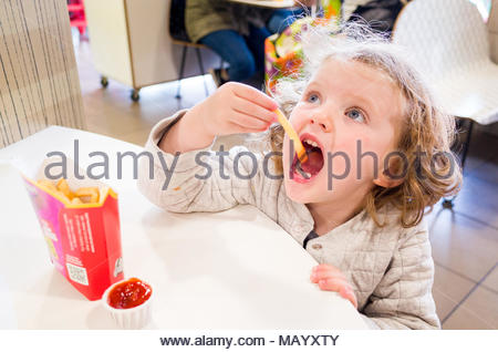 Toddler eating McDonald's french fries, UK - Stock Photo