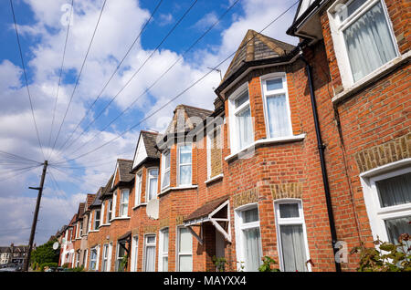 Telephone cables running from post to terraced houses, Haringey, North London, UK - Stock Photo