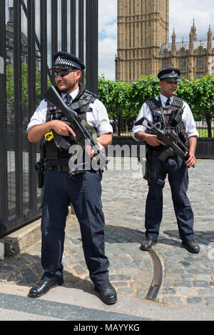 Armed police officers outside the Houses of Parliament, London, UK - Stock Photo