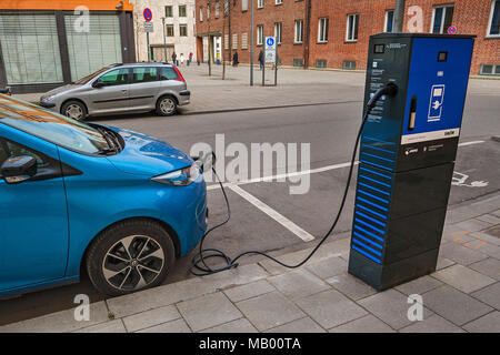 Electric car is charged at green electricity charging station with charging cable, Munich, Bavaria, Germany