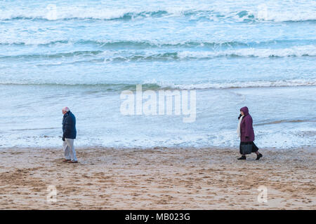 A man walking along Fistral Beach with his wife following behind in Newquay in Cornwall. - Stock Photo