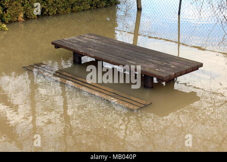 Outdoor wooden table and two benches in front of hedge flooded during heavy rain with trees and wire fence reflection - Stock Photo