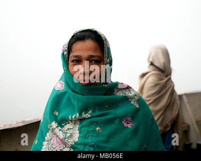 A woman of the third class of 'MV Bangali', a ferry on route from Dhaka to Morelganj seen smiling. Bangladesh is a country on water. With huge portion of its territory in the river delta of Ganga (which is called Padma here) and Brahmaputra, people have to live on water and rely on water transport. Huge ferries 'made in Bangladesh' leave river ports to transport tens of thousands of passengers every day to their destinations. Most of them just with poor - or none - radar equipment. Although many bad news about accidents, the fact is, that the river transport still remains the safest and effect - Stock Photo