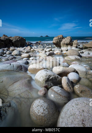 the beautiful and atmospheric scenery at porth nanven in the cot valley neat cape cornwall st just on the cornish coastline. large pebbles on beach. - Stock Photo