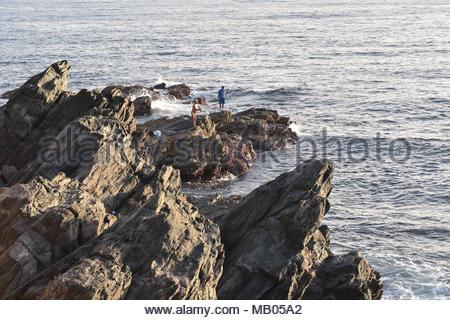 Volcanic rocks men fishing on the Atlantic coast near Las Palmas Gran Canaria Canary Islands Spain. - Stock Photo