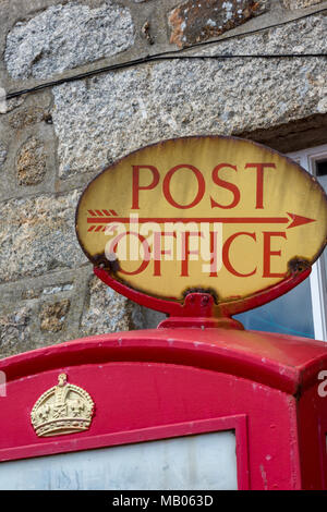an old vintage post office or postal services signpost on the top of a traditional red gpo post office phone box. English typically British telephone. - Stock Photo