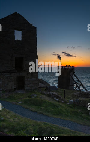 The abandoned or disused historic tin mine engine houses and buildings on the Cornish coast in west cornwall at sunset in silhouette against the sky. - Stock Photo