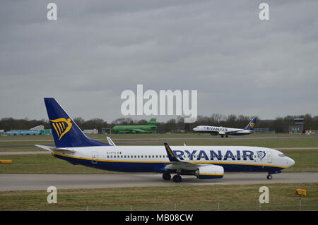 Ryanair aircraft taxiing in at London Stansted Airport as another Ryanair plane takes off in the background - Stock Photo