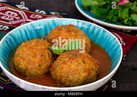 Close up of Koofteh Tabrizi Large Meatballs Stuffed With Dried Fruits, Berries And Nuts In Tomato Turmeric Broth A Traditional Azeri And Iranian Dish  - Stock Photo