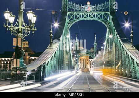 Budapest at night. Tram on old iron bridge - Szabadsag hid (Liberty bridge). - Stock Photo