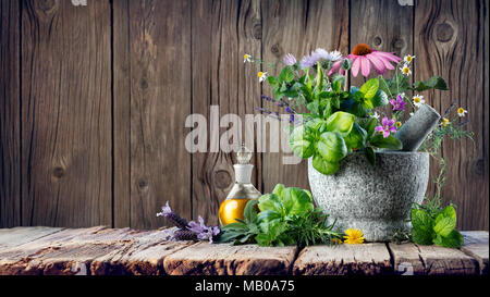 Healing Herbs And Essential Oil In Bottle With Mortar - Homeopathy and Alternative Medicine - Stock Photo