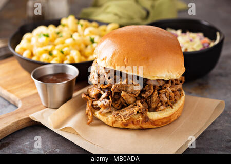 Pulled pork sandwich with bbq sauce on the table - Stock Photo