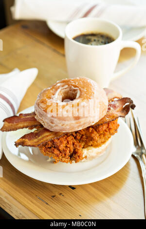 Hot spicy fried chicken and bacon sandwich in a donut with a cup of coffee - Stock Photo