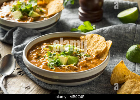 Spicy Homemade Tortilla Soup with Cheese Cilantro and Lime - Stock Photo