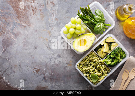 Vegan meal prep containers with pasta with green pesto sauce and vegetables - Stock Photo