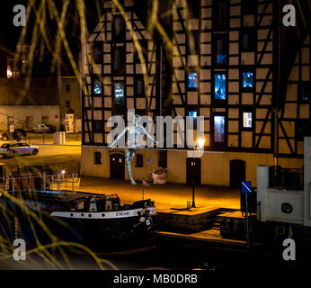 Sculpture 'Man crossing the river' in front of granaries at night in Bydgoszcz, Poland - Stock Photo