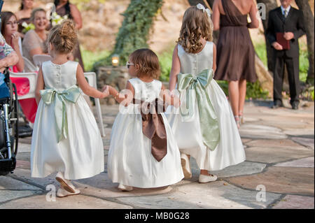 Three little cute girls holding hands and walking the aisle at an outdoor wedding at California - Stock Photo