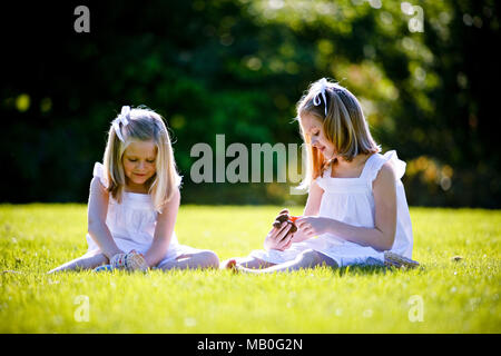Two young pretty Caucansian girls in white skirts sitting on grass playing at a park with back lighting and blurry green background - Stock Photo