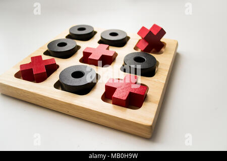 Wooden tic tac toe game on white background. Red crosses and black noughts - Stock Photo