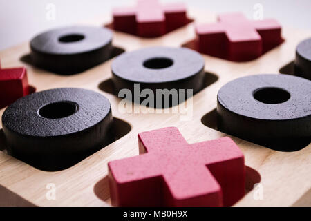 Wooden tic tac toe game on white background. Red crosses and black noughts. Closeup photo - Stock Photo