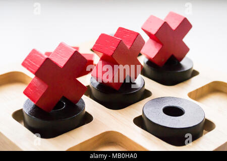 Wooden tic tac toe game on white background. Three red crosses on black noughts. - Stock Photo