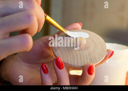 Woman painting wooden cap in white. Handmade, diy, Closeup photo. - Stock Photo