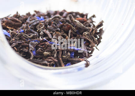 Dried herbal bergamot tea leaves in transparent glass jar on light background - Stock Photo