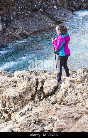 Woman standing on rocks at Fairy Pools, river Brittle, Isle of Skye, Scotland, UK in March - Stock Photo