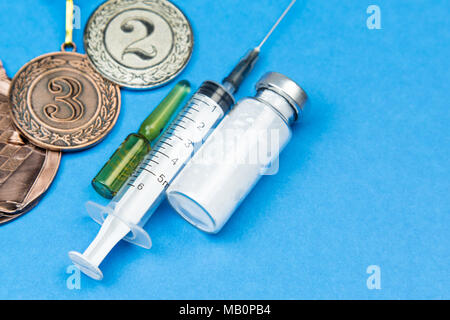 Prohibited drugs to increase athletic performance in the competition. Syringe, medicine on a blue background. - Stock Photo