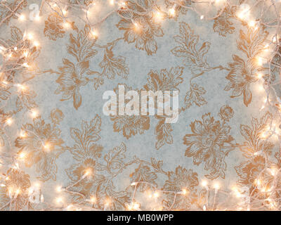 Vintage gold floral wallpaper background with holiday white lights frame. - Stock Photo