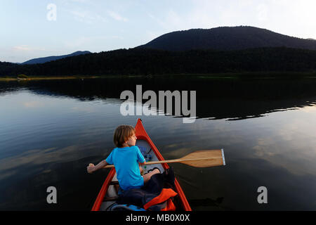Young boy paddling in a canoe on a lake at twilight - Stock Photo